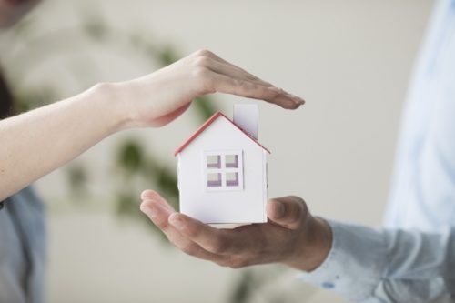 close-up-hands-protecting-small-house-model_23-2148204008