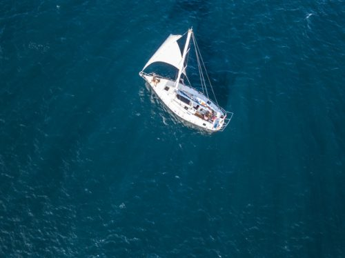 lonely isolated yacht under the sail with tall mast going in still sea aerial top view