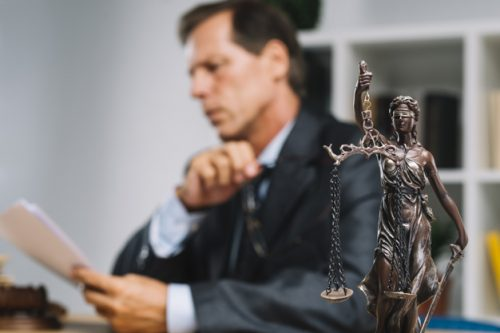 professional-lawyer-reading-document-with-justice-statue-forefront_23-2147898485